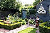 Mit Buchshecken begrenzte Beete in Garten mit blau lasiertem Holzschuppen
