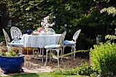 Runder Tisch und Gartenstühle aus weiss lackiertem Schmiedeeisen, gedeckt zur Teatime im Garten