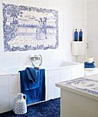 Weisses Bad mit Accessoires in kräftigem Blau und altem Fliesenbild über der Badewanne im zartblauen, klassischen Delfter Muster