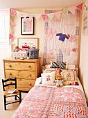 Rustikales Kinderzimmer - Bett mit Patchworkdecke neben schlichter Holzkommode und Wimpelgirlande vor Wandbehang
