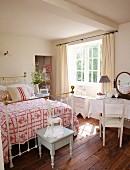 Weisser Holzhocker vor Bett mit Messing Gestell im traditionellen Schlafzimmer
