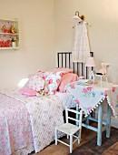 Ländliche Kinderzimmerecke mit Blumenmotiven - Beistelltisch neben Kinderbett mit Blumenmuster auf Tagesdecke und Kissen