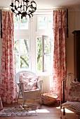 Weisser Korbstuhl vor Fenster mit bodenlangen Vorhängen im traditionellen Schlafzimmer