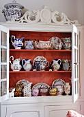 Weisser Küchenschrank mit Schnitzereien und Blick durch offene Türen auf antiquarische Porzellansammlung