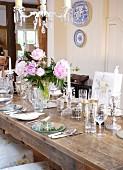 Rustikaler Tisch mit Gedecken und verschiedenen Gläsern in ländlichem Esszimmer