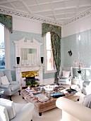 Elegante hellgraue Polstermöbel um gepolstertem Couchtisch in traditionellem Wohnzimmer mit offenem Kamin