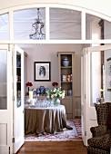 Blick durch offene Flügeltür auf Tisch mit bodenlanger Tischdecke im traditionellen Salon