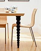 Korbstuhl an Esstisch aus Holz mit schwarzen, gedrechselten Tischbeinen (Ausschnitt)