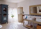 Badezimmer im Landhausstil mit Doppelwaschbecken, Holzspiegel & antikem blauen Holzschrank