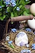Mit Vergissmeinnichtblüten dekoriertes Osterei in Körbchen