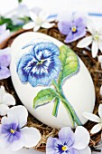 Goose egg decorated with pansy using napkin decoupage