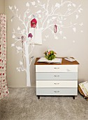 Chest of drawers and painted tree with coat hooks in teenager's bedroom