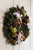 Wreath with festive decorations on white front door