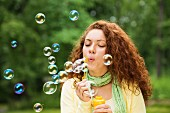 Woman blowing soap bubbles into the air