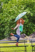 Woman with umbrella skipping through park