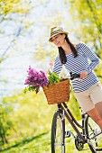 Woman pushing bicycle with spring flowers in basket