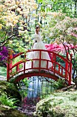 Bride in white wedding dress standing on red bridge in park