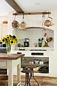 Country-house kitchen with masonry hob area decorated with nostalgic copper pots and pans