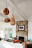 Fishing hut converted into weekend cottage with exposed, white-painted roof and pendant lamps with wooden lampshades above seating area with stone chimney breast