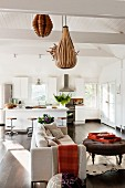 Artistic chipboard lampshades above pale sofa and ottoman, island kitchen counter with bar stools in background