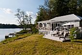 Zu Wochenendhaus ausgebaute Fischerhütte im weissen Long- Island-Stil am See; Plattform mit Liegestühlen und überdachte Eingangsveranda