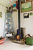 Cosy, cabin atmosphere with fire in nostalgic iron stove and light blue corner shelves in renovated shepherd's hut