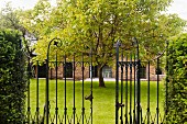 Open wrought iron gate leading to garden with tree and English house with brick facade