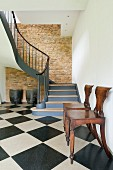 Elegant winding staircase in converted barn with exposed masonry wall