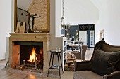 Fire burning in open fireplace in open-plan, loft-style living room with antique upholstered furniture and designer kitchen in background