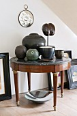 Round, antique side table with marble top decorated with various ceramic vases and objets d'art