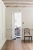 Eine in der weißen Holzvertäfelung versteckte Tür öfffnet sich zum Gästebad in einem minimalistisch elegantem Landhaus Flur
