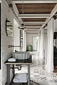 Wash basin on simple table with wall-mounted taps in tiled corridor area opposite open curtains used as partition