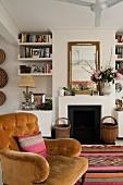 Living room with open fireplace, bookshelves and nostalgic velvet armchair on Moroccan rug