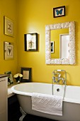 Nostalgic bathtub against yellow wall decorated with pictures of insects and mirror with shell-mosaic frame