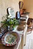 Stone sink unit and hand-painted crockery in Mediterranean holiday home