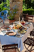 Garden table set with colourful crockery in summery, Mediterranean atmosphere