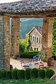 Festively set table under rustic tiled roof of terrace in summery, Italian landscape