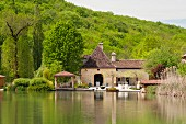 17th century, French mill seen across lake; hilly Dordogne landscape in background