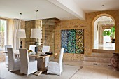Elegant dining area with loose-covered chairs and standard lamps in front of glass partition and staircase; triptych on stone wall and view through antique arched doorway
