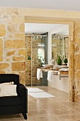 Open doorway in stone wall with view of washstand and shower in modern bathroom; armchair in foreground