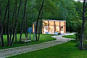 Contemporary studio building with terrace in idyllic grounds of old mill in the Dordogne; bench and sculptures next to path below trees