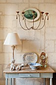 Nostalgic, shabby-chic table with drawer decorated with table lamp, antique crockery and ornamental shells against limestone wall