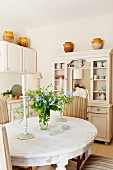 Dining room with country-house-style ceramic pots on dresser and candlesticks and flowers on oval dining table