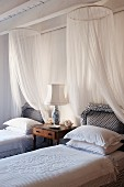 Two elegant, country-house-style twin beds with white mosquito nets either side of antique bedside table