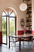 Delicate metal chairs around table in corner of room with open, arched, glass double doors and view into garden
