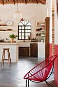 Sessel mit roter Seilbespannung und Metallgestell auf Estrichboden vor minimalistischem Kochbereich