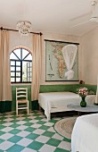 Green and white chequered floor in bedroom with twin beds and arched window