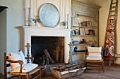 Rush-bottom armchairs with wooden frames flanking open fireplace and antique wooden shelves in rustic living room