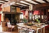 Grosse Wohnküche im französischen Landhaus mit alten Deckenbalken und Holzofen