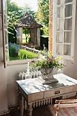 Bouquet of garden flowers on simple writing desk below open window with view of garden
